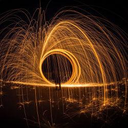 Fire Artist Spinning Sparks at Night